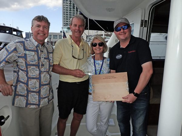 Picture of Jeff, Ryan, Mike and Patsy on boat being given award for Nordhavn 47