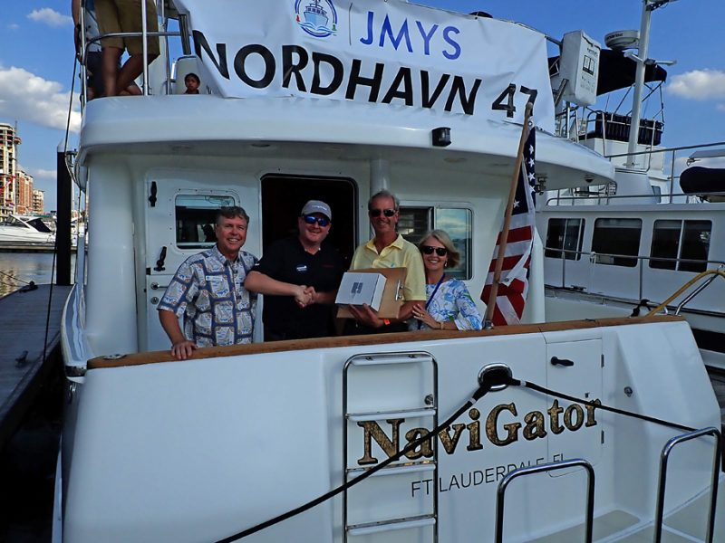 Picture of Jeff, Ryan, Mike and Patsy on boat being given award on Nordhavn 47